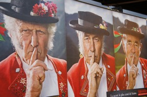 Publicidad suiza en una estación de tren (los hombres van vestidos de la forma tradicional de una región)