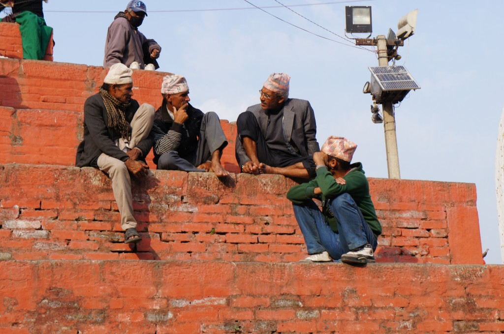 A common routine: Sit and talk with your peers on temple´s stairs. These men are wearing the traditional Nepali hat.